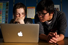 TIMES PHOTO: JAIME VALDEZ - Sixth-grader Parker Johnson listens as Oregon Tech student Huy Le offers his help during a coding class at Hazelbrook Middle School.