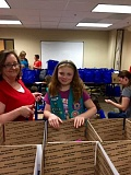 SUBMITTED PHOTOS - Members of Girl Scout Troop 45060 brought two cars full of supplies and cookies to Camp Courage earlier this month. The supplies were packed into care packages, which were sent to soldiers stationed all over the world.