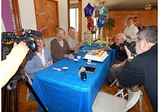 PMG PHOTO: BARBARA SHERMAN - Curtis Tigard (center of table) enjoys the festivities with (from left) daughter-in-law Sandra, son David, best friend Bud Ossey and Dottie Buss, who helped organize the party, as KGW's Christine Pitawanich (left) film and Phil Pasteris (right) shoots photos at the Royal Villas party.