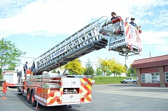 SPOTLIGHT PHOTO: COURTNEY VAUGHN - Firefighters test out a newly acquired ladder truck at the Scappoose Fire station in Scappoose. The truck was donated to the district by Portland Fire & Rescue.