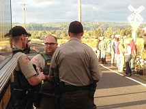 Sheriff's deputies discuss strategy for addressing a trespassing and criminal mischief incident on railroad property on Kallunki Road in the Quincy area during a protest gathering in 2014. The city of Clatskanie is considering restructuring its police department and contracting with Columbia County Sheriff's Office for law enforcement coverage.