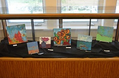 SPOTLIGHT PHOTO: NICOLE THILL - A display case at the St. Helens Public Library showcases mixed-media pieces by Luanne Kreutzer. Many of the pieces are available for sale.