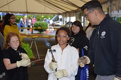 COURTNEY VAUGHN - Olivia Fowlkes, 10, with the supervision of Joel Gonzalez (right) holds a torch used in roofing and weatherproofing during a women in trades career fair held in Portland last Saturday, May 14.
