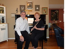 BARBARA SHERMAN - Gerry Craig and Nancy Vink, holding her flute, sit on a piano bench in his home with photos of his piano-playing mother and grandmother behind them.