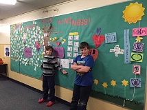 SUBMITTED PHOTO  - Forest Hills Elementary fifth-graders Eric Newheiser, left, and Oberon McDaniel have created a Kindness Board at the LOACC. Post notes about the acts of kindness you witness.