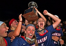 VERN UYEATKE - Lake Oswego celebrates with the girls lacrosse state championship trophy it earned with a 12-8 victory over West Linn on Wednesday.