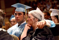 REVIEW PHOTO: VERN UYETAKE - Lakeridge High School receptionist JJ Elske's son Dutton Elske, the oldest of her three kids, enjoys commencement on June 3 with his mom at his side.
