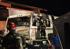 COURTESY PHOTO: HILLSBORO FIRE & RESCUE - A firefighter extinguishes hot spots after a motor home fire in a commercial storage yard Friday night in Hillsboro.