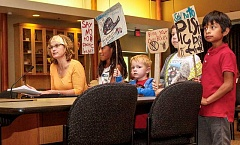 NEWS-TIMES PHOTO: TRAVIS LOOSE - Sustainability activist Elaine Cole, backed by her children and their friends, testifies in favor of the plastic bag ban.