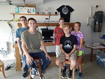 BARBARA SHERMAN - In the Bigelow family garage that doubles as the Fourth Moon Design production center are (from left) Jackson Gallahan, Christian Birbeck wearing a shirt with the company logo, Spencer Sproul and Peter Bigelow plus Kelly Roth, who does the photography for the website; on the wall behind them is their first screen-printed T-shirt.