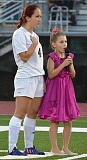 COURTESY PHOTO: SIMON DATE - Ruby Date, right, pictured singing the national anthem at the unveiling of St. Helens High School's new turf field next to her idol and graduated Lions senior Ashley Giesbers (left), has autism and is excited to help friends and peers live their soccer dreams.