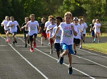 SPOKESMAN PHOTO: VERN UYETAKE - Corbin Stoddard leads the third grade group around the track during its division race at the Wilsonville Kiwanis Fun Run July 30.