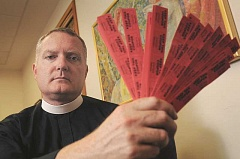 REVIEW PHOTO: VERN UUYETAKE - The Rev. Jeremy Lucas of Christ Church Episcopal Parish in Lake Oswego holds the 150 tickets he purchased in an all-star softball teams raffle. The prize was an AR-15 assault rifle that Lucas says he hopes to turn into a piece or pieces of art, but the pastor's handling of the weapon after taking possession is now being investigated.