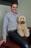 REVIEW PHOTO: VERN UYETAKE - Charlie the labradoodle sits on Dr. Tim Saruk's lap during a photo session in June. The therapy dog was killed Aug. 15 after being hit by a car near his home.