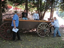 PHOTO BY ELLEN SPITALERI - Jerry Herrmann, left, watches as crew members push a replica wagon into place at the End of the Oregon Trail Interpretive Center. Pictured, left to right, are Lucio Perez, Gabriel Gunvaldson, Craig Holfeld, Owen Civica, Isaac Ehrich and Cody Carver.