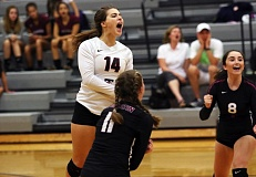 DAN BROOD - Tualatin senior libero Jordan Mitchell (14), freshman Jackie Phillips (11) and junior Sofia Ashley celebrate a point late in the contest during the Timberwolves' five-set win at Sherwood.