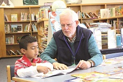 INDEPENDENT FILE PHOTO - A volunteer reads with a student at Washington Elementary School through the Start Making a Reader Today program. SMART is now looking to expand to serve the Gervais Elementary School community.