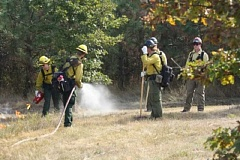 PAM FARRIS/FOR THE REGAL COURIER - Firefighters simultaneously light a presribed burn (far left) and water down trees (second from left) while others stand by ready to tamp out the fire if it spreads in the wrong direction at the Tualatin River National Wildlife Refuge on Sept. 29.