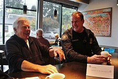 CONNECTION PHOTO: KELSEY O'HALLORAN - Multnomah resident Sim Hyde (left) shares a laugh with Portland Police Officer Ryan Engweiler during Coffee With a Cop Oct. 7 in Multnomah Village.