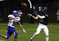 DAN BROOD - Tigard senior Aksel Thorsfeldt (right) pulls in a 20-yard touchdown pass in front of McNary senior Isaiah Rhodes.