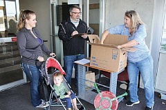 HOLLY M. GILL - Brian Crow, center, tallies up the purchases from Sue Vanek, at right, who was accompanied by her daughter, Kelsey Parsons, and grandson, Jase, 17 months. Vanek bought a Christmas tree stand, bathroom fixtures, and a door lock.
