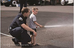 DAVE JACKSON - A Molalla firefighter at last year's National Night Out gave kids a chance to man a fire hose.