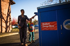 TIMES PHOTO: ADAM WICKHAM - Lawanda Ollison drops off her ballot with her son Otis Ollison-Lewis at the drop box outside Tigard City Hall in last year's general election.