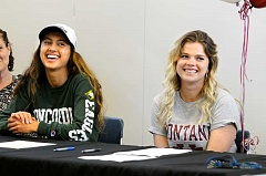 SETH GORDON - Newberg High School seniors Madison Hergert and Natalie Peterson are all smiles at their signing ceremony last month Hergert will run for Concordia-Irvine in California and Peterson will throw javelin at the University of Montana.