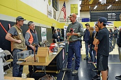 SPOTLIGHT PHOTO: NICOLE THILL - Jake Feakin, a Columbia River People's Utility District lineman; Jake Carter, a business representative from the International Brotherhood of Electrical Workers and a PUD board director; and Andy Larson, a West Oregon Electric Cooperative lineman, speak with a group of high school students at a career expo Tuesday, April 26. Feakin later showed the students some of his work equipment and explained what he does as a lineman.