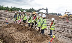 TIMES PHOTO: JONATHAN HOUSE - Beaverton School District students pose for a photo with Charli Hagseth at the construction site of a new elementary school on Tuesday.