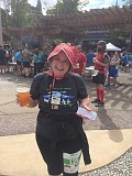 Editor Lindsay Keefer, wearing a bonnet, Oregon Trail 5K T-shirt and 'medal' in the shape of a floppy disc like the game its named after, receives a celebratory free beer after completing her first 5K run in Oregon City.
