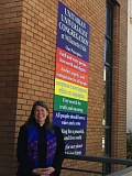 SUBMITTED PHOTO - Marcia Stanard, the minister at Unitarian Universalist Congregation at Willamette Falls, stands in front of a sign at 710 Sixth St., Oregon City, based on Unitarian Universalist principles.