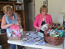 PHOTO BY ELLEN SPITALERI - Jerri Adams and Sandra Brown put finishing touches on two other baskets donated by Oregon Womans Club members.