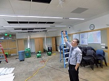 GAZETTE PHOTO: RAY PITZ - City Manager Joe Gall points to where an InFocus projector once was in the ceiling of the Sherwood City Council chambers/community room. A suspected second-floor faucet is being blamed for flooding of the council chambers at Sherwood City Hall over the weekend.