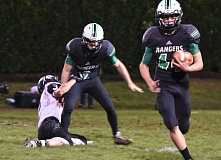 ESTACADA NEWS: HEATHER TREANOR - Estacada running back Wyatt Riedel takes the pitch and heads around the corner during the Rangers 26-6 home playoff win Friday.