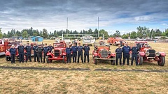 SUBMITTED PHOTO  - TVFR volunteers stand with the department's antique apparatus fleet at the Newberg Old Fashioned Festival.