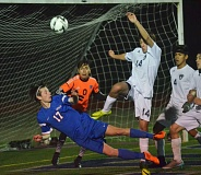 PAMPLIN MEDIA: COREY BUCHANAN - La Salle Prep's Tanner Rast (17) lunges for the ball in front of Wilsonville goalkeeper Oscar Baron-Soto (0) and midfielder Sam Blohn (14) during Tuesday's OSAA Class 5A boys' soccer semifinal.