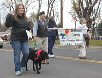 SUSAN MATHENY - From left, Veterans Service Office staff members Laura Moore, Tom Weiss, and Scottie Henry, at far right, walk and carry their banner in the American Legion Veterans Day Parade on Nov. 11.