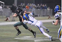 PAMPLIN MEDIA GROUP: SETH GORDON - Tigard High School senior running back Ryan Minniti (left) looks to get away from Newberg senior Anthony Adams during Friday's state playoff game. Tigard won 46-26.