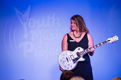 SUBMITTED PHOTO: JASON DESOMER PHOTOGRAPHY - Rachael Sneddon holds a KISS guitar, up for auction at the Youth Music Partnership.