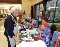 BARBARA SHERMAN - Holiday Bazaar organizer Jenny Reiser (left) chats with vendor Norma Gronholme during the senior center's annual event that benefits the Friends of the Sherwood Senior Center.