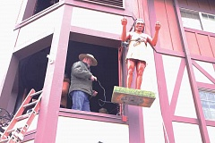 LINDSAY KEEFER - Volunteers use a pulley system to lift an American Indian statue into the Glockenspiel clock tower.