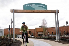 FILE - A bicyclist rides through the entrance to the new segment of the Tualatin River Greenway Trail at Barngrover Way.