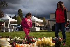 TIMES FILE PHOTO: ADAM WICKHAM - Makenna Ruiz and her mother, Tabatha, look at flower bouquets at the Tigard Farmers Market in 2015.