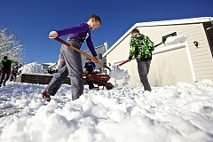 TIMES PHOTO: JAIME VALDEZ - Marcus Merritt, 12, helps his friends Aiden and Finn Kelly shovel their grandpa's driveway in Sherwood after last week's snowstorm.