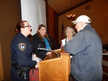 BARBARA SHERMAN - Tigard police officer Kary Bowman (left) and Det. Julie Hicks talk to a couple in the Summerfield Clubhouse following their Feb. 10 presentation about not falling victim to a scam.