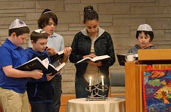 STAFF PHOTOS: VERN UYETAKE - From left, Josh Hershinow, Tate Williams, Max Niedergang, Nay Nay Kent-Taylor and Jeremy McMullen perform the blessing of the candles.