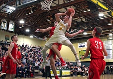 TIDINGS PHOTO: MILES VANCE - West Linn guard Braden Olsen hangs in the air to score during his team's 76-65 win over Lincoln in the second round of the Class 6A state playoffs at West Linn High School on Friday night.
