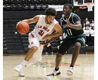 PAMPLIN MEDIA GROUP: JIM BESEDA - La Salle Prep's Jonah Pemberton drives against Parkrose's NaShawn Penney during the second quarter of Friday's OSAA Class 4A boys basketball third-place game at Gill Coliseum.