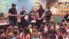 COURTESY PHOTO: SHERIE MORAN - North Marion High School students and Aurora American Legion Auxiliary member Beverlee Koutny present flag stands to second-graders.